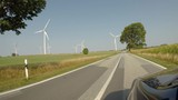 Driving shot passing Wind Turbines Spinning on Country Road 4K UHD - 232897969