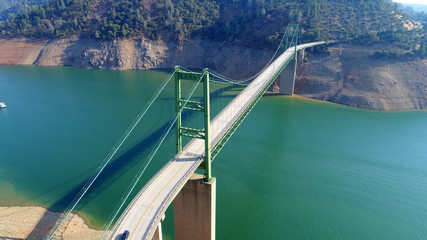 drone view of a green suspension bridge crossing a lake © georowe