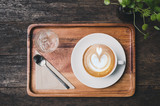 Top view of hot coffee cup with cold water and spoon on wood tray on grunge dark brown wooden table with green plant in cafe. - 232904191