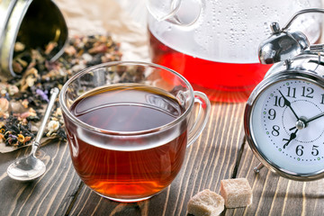 Time to drink tea. A cup and teapot of hot flower tea and an alarm clock. Morning tea.