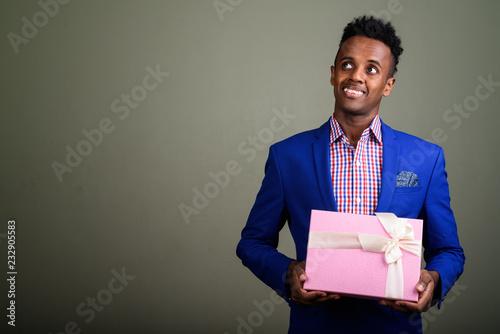 Młody przystojny Afrykański biznesmena mienia prezenta pudełko przeciw colo