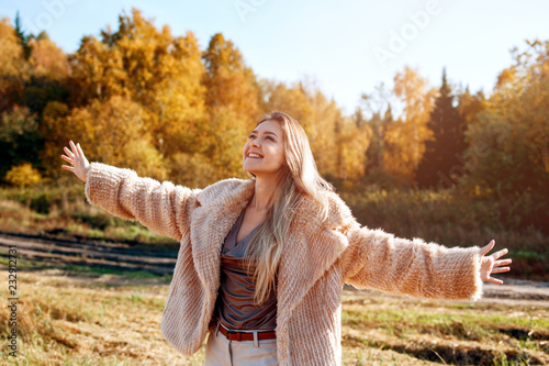 Foto Murales Cheerful girl with raised hands on the field in warm autumn season.