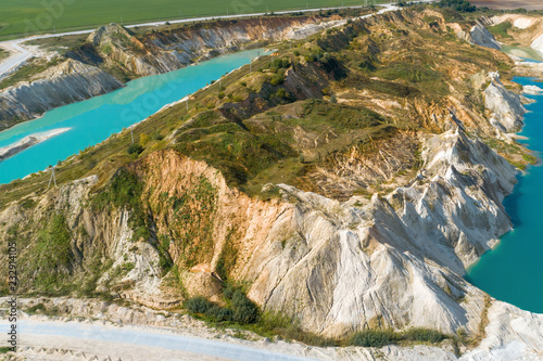 An old gypsum quarry filled with blue and pure water. Aerial view, from top to bottom
