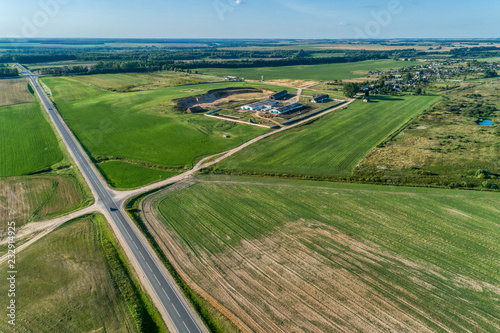 Foto Murales Green agricultural and wheat field. The fields are separated by asphalt road. View from a great height