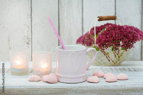 Kobiecy martwej natury ze świecami, kubek serca, cukierki w kształcie serca i kosz z kwiatami w pastelowych odcieniach różu