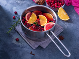 Mulled wine in cooking saucepan with fruits and cranberries, hot winter drink