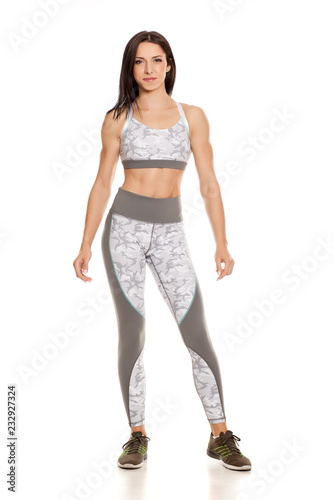 Wall mural Pretty muscular young woman posing on white background