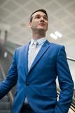 Businessman holding a trolley on an escalator - 232939379