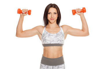 Pretty muscular young woman holding weight on white background © vladimirfloyd