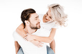Handsome young adult man giving piggyback to wonderful blonde woman isolated on white - 232945513