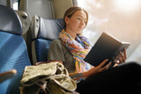 Relaxed young woman reading on the train - 232945707