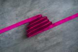 Pink velvet ribbon in shape of Christmas tree on dark gray background. Copyspace for text, horizontal overhead - 232947111