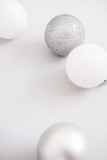 White Christmas background. Glossy silver and glitter decoration balls. Minimalist style. Copyspace for text, overhead - 232947385