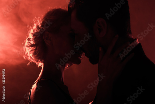 Leinwandbild Motiv Attractive young couple almost kissing on red smoke background