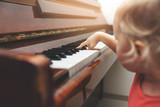 music education - child pushing piano keys - 232954173