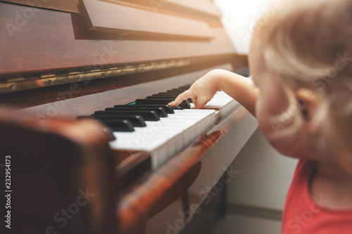music education - child pushing piano keys © ronstik