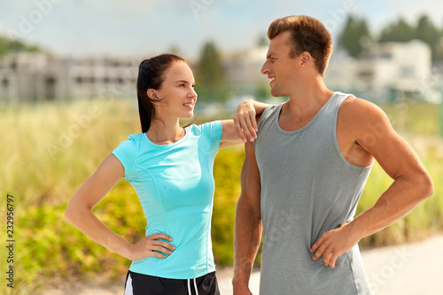 Sticker fitness, sport and lifestyle concept - happy couple in sports clothes outdoors