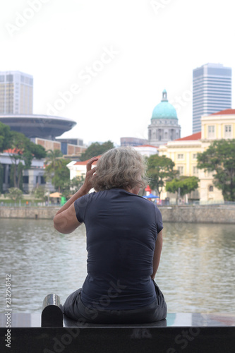 Tourist sitting and looking at the skyscrapers of Singapore