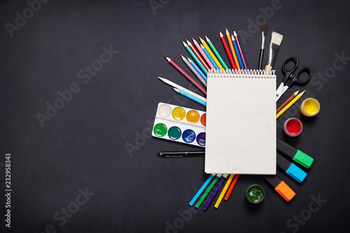 Drawing supplies, empty drawing pad on blackboard. Artist's set. Back to school.
