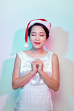 Young asian woman in sexy white dress and santa hat praying isolated on white background - 232961173
