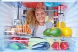 Woman standing in front of fridge full of groceries and looking something to eat. Picture taken from the inside of fridge. - 232962135