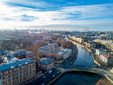 Aerial; drone view of river channel in historical city part with bridges and old house facades near embankment; port with loading cranes and shipyards, wharf on the background; sunny autumn day - 232962580