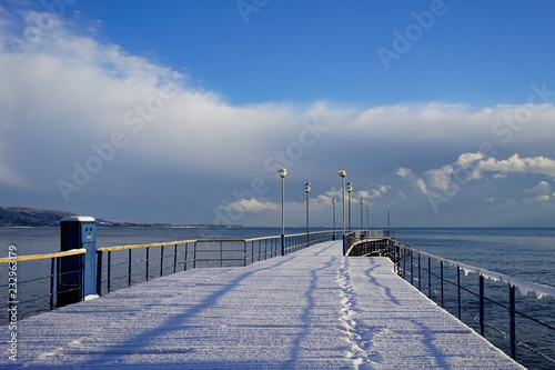 winter landscape with pier in the background of sea and sky.