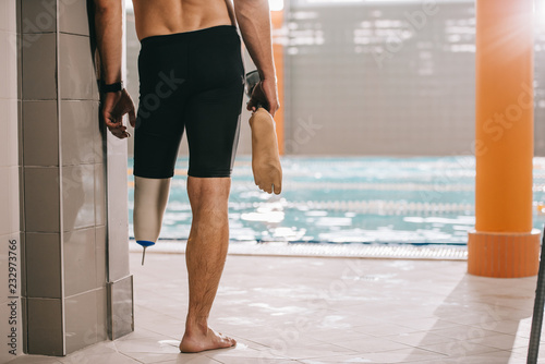 Sticker cropped shot of athletic swimmer standing at poolside of indoor swimming pool and holding his artificial leg