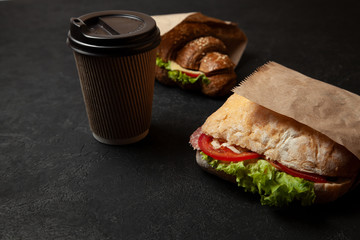 Sandwich and cup of coffee on black background. Morning breakfast or snack when hungry. Street food to go