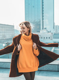A beautiful young girl blonde walks through the streets of the city, smiling, waving her coat. She is wearing an orange sweater and black tights, a red coat. Street casual style. Emotion of joy © Yevhen