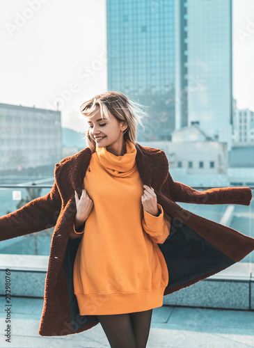 obraz lub plakat A beautiful young girl blonde walks through the streets of the city, smiling, waving her coat. She is wearing an orange sweater and black tights, a red coat. Street casual style. Emotion of joy