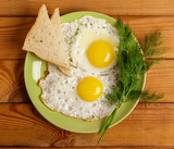 Fried eggs of 2 eggs with a piece of bread, dill on the table. - 232989163