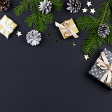Festive Christmas background with fir branches, presents, decorations on black, copy space - 232994586
