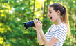 Young woman with a professional digital SLR camera on a bright summer day in the forest