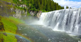 Mesa Falls, Idaho, USA - Wide Waterfalls Surrounded By Green Pine Trees With A Rainbow