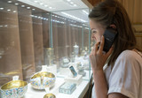 Woman in museum with handheld audio guide device. - 232997962