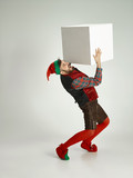 The happy smiling friendly man dressed like a funny gnome or elf posing on an isolated gray studio background. The winter, holiday, christmas concept - 232998548