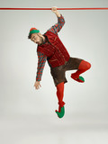 The happy smiling friendly man dressed like a funny gnome or elf hanging on an isolated gray studio background. The winter, holiday, christmas concept - 232998577