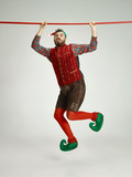 The happy smiling friendly man dressed like a funny gnome or elf hanging on an isolated gray studio background. The winter, holiday, christmas concept - 232999341