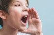 Boy screams with his hand near his mouth