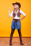 Beautiful young woman wearing cowboy costume over yellow background. Silly moment - 233006950