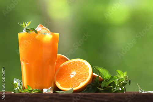 Fresh orange juice in glass with sliced orange on wood and nature background - 233016774