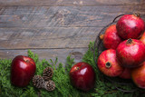Festive colorful botanical Christmas composition. Fresh green juniper red apples pomegranates in wire basket pine cones on aged plank wood background.Frame with copy space - 233018319