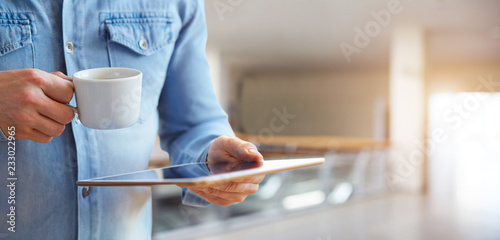 Male hands holding white digital tablet and cup of coffee - 233022965