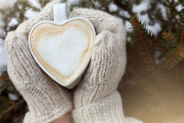 warming atmosphere with a favorite drink hot mug of frothy cappuccino in hands dressed in mittens against the background of an evergreen tree in winter