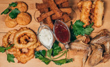 breaded appetizers, fried chicken wings and breadcrumbs with sauce on a wooden Board - 233027309
