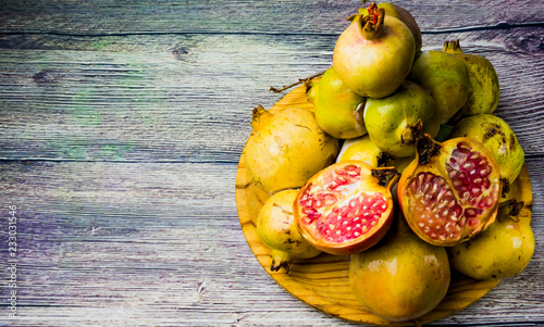 Foto Murales Pomegranate fruit on a wooden plate