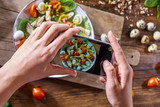 Hands of a girl with a phone make a photo of a freshly prepared salad. Food blogging concept. Top view - 233035743