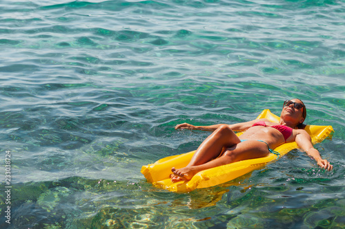 Foto Murales Young woman floating on the mattress in the sea