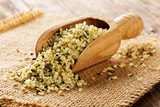 Heap of raw, organic hemp seeds in wooden scoop on burlap on rustic table - 233040362